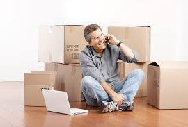moving boxes stacked near man on phone